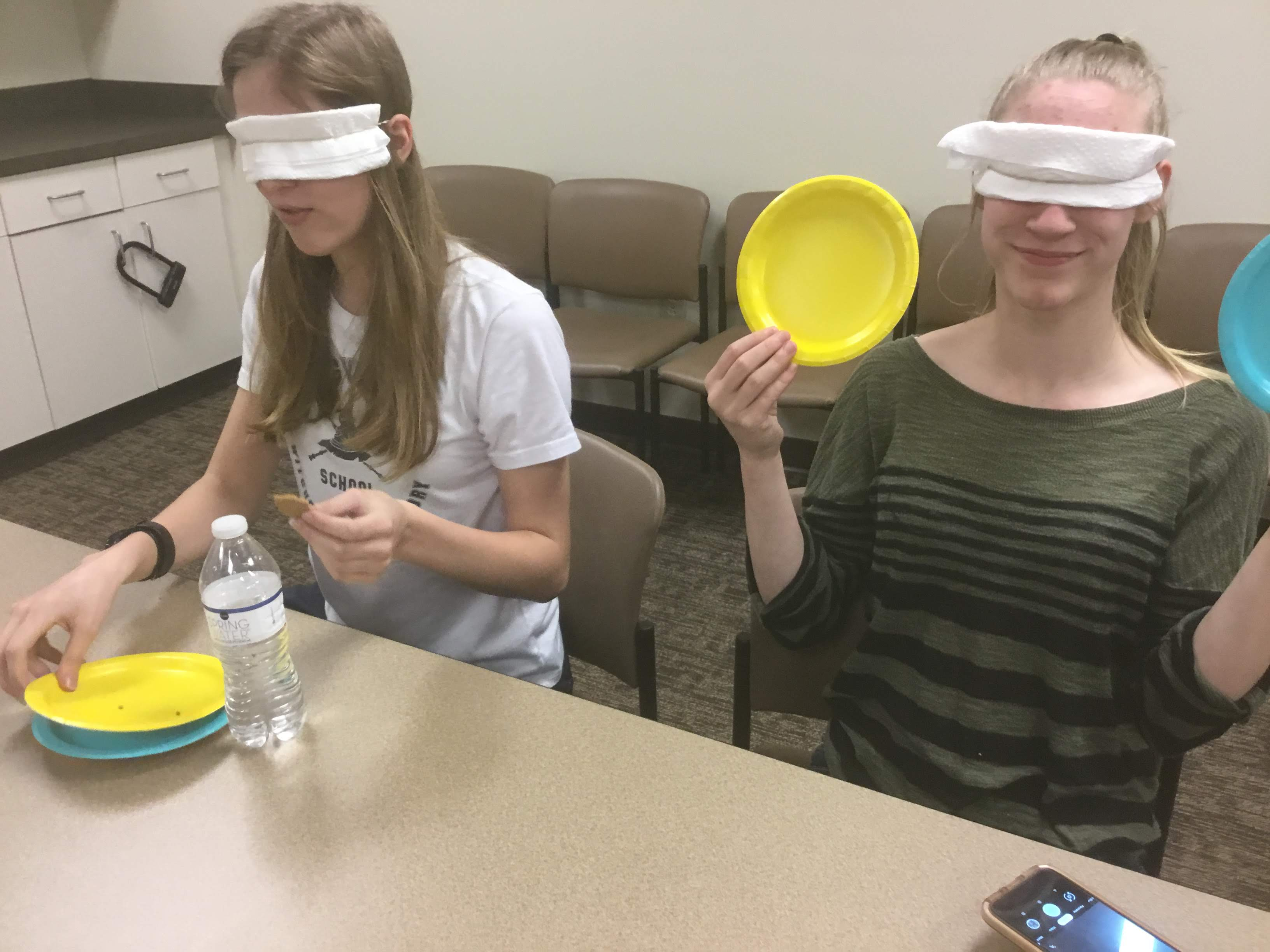 Two blindfolded teens seated at a table; each has two small paper plates in front of them.