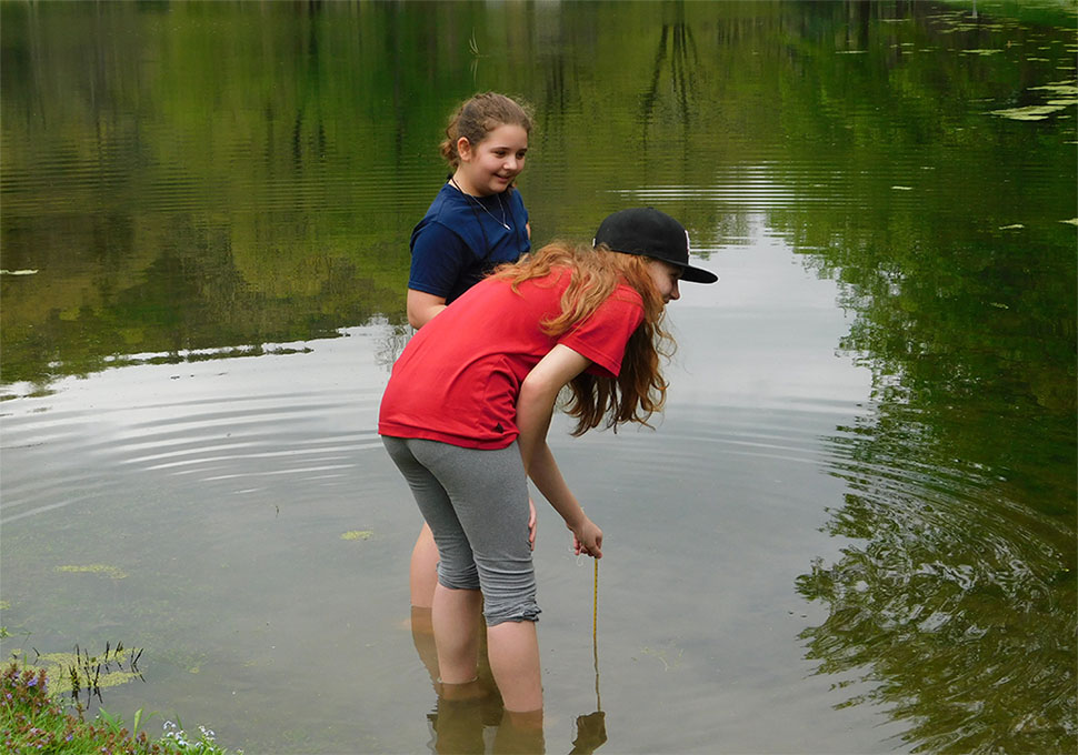 taking the water temperature of the pond