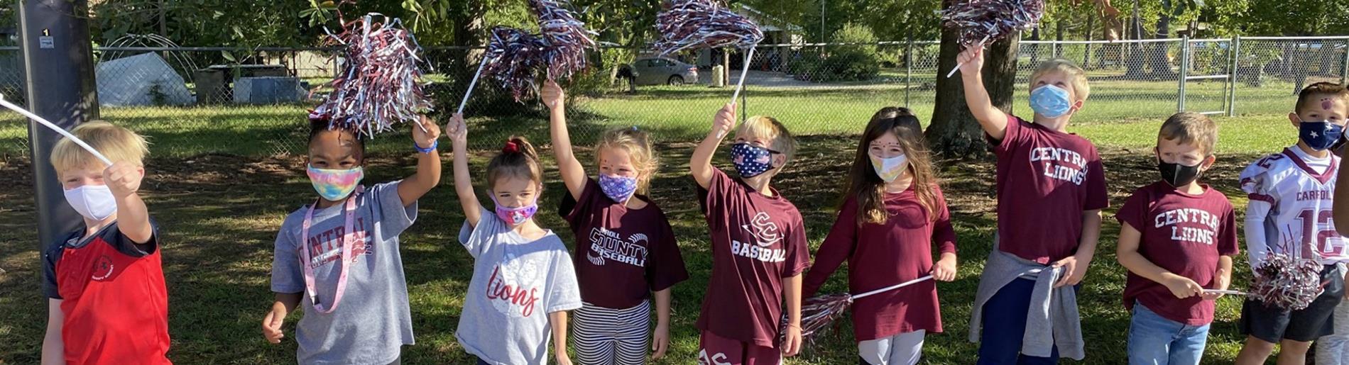 First grade students waving pom poms