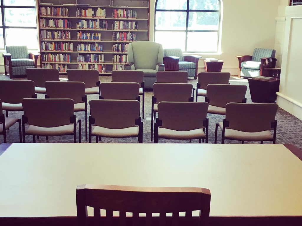 space set up with rows of straight backed wooden chairs facing an upholstered arm chair for an author reading at Spanish Fort Public Library
