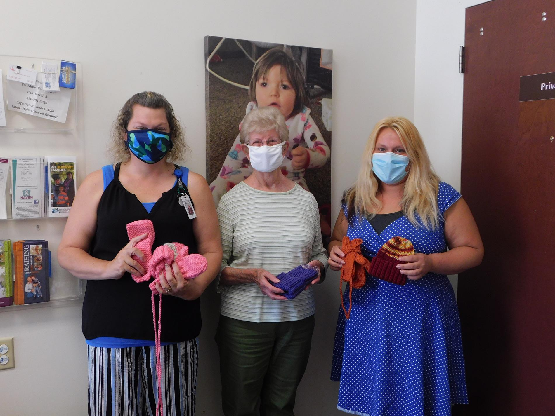 Jody Tice and Apryl Tubbs, Family Services Supervisors, are excited to receive hats, mittens, and slippers from knitter Mary Lou Davis of Wellsboro.