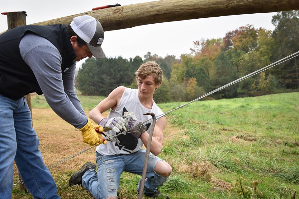 Student Assists in Putting Up Fence