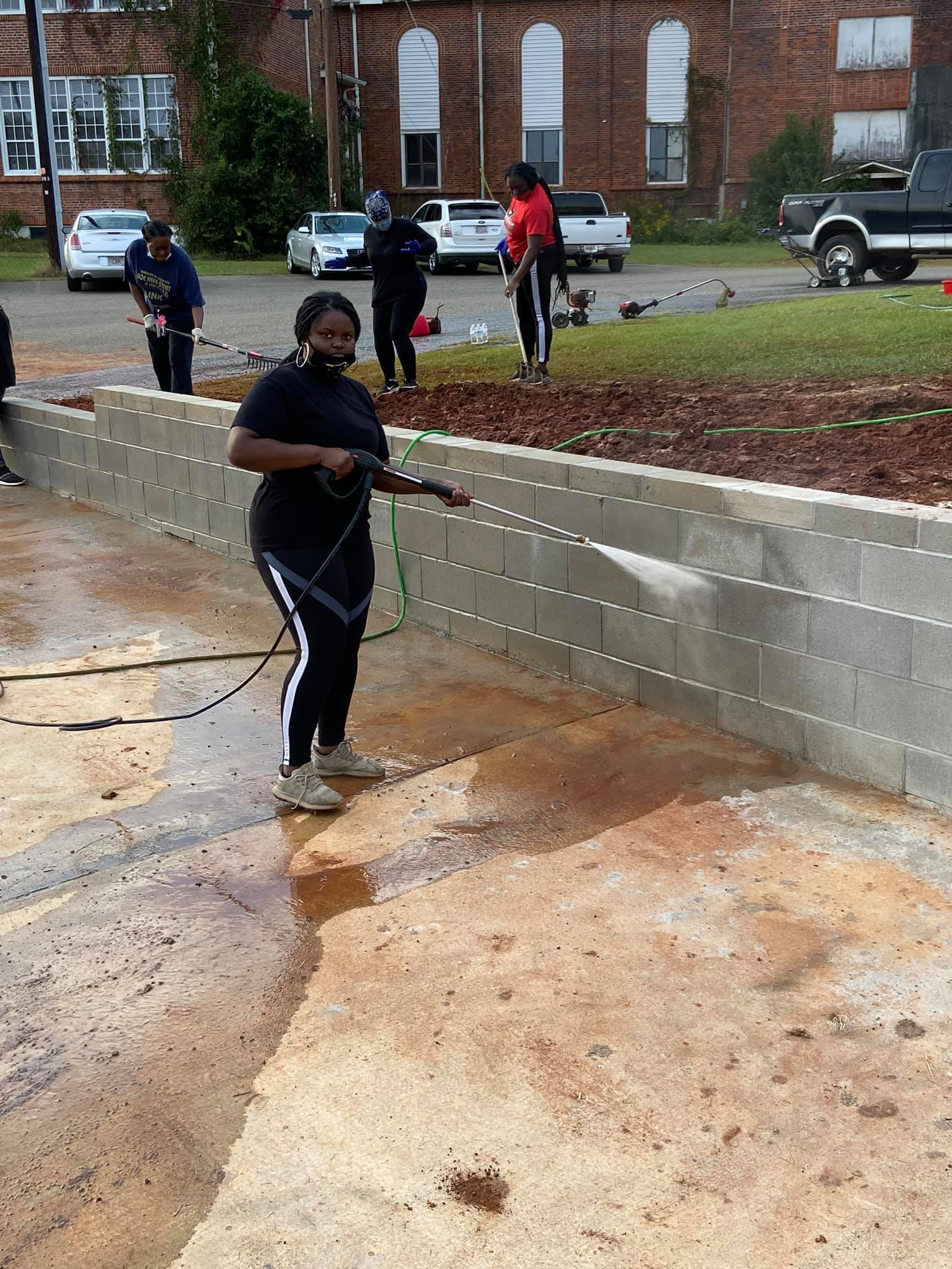 Ms. Starling pressure washing the retainer wall.