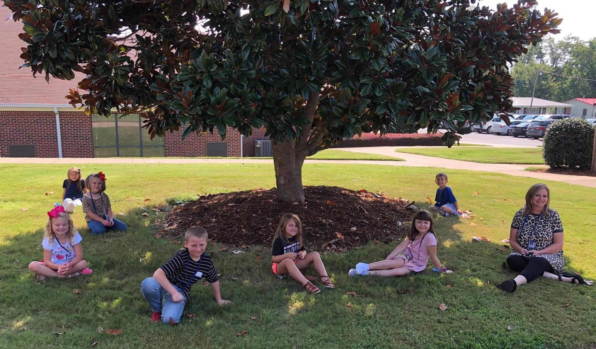 First grade relaxing under tree