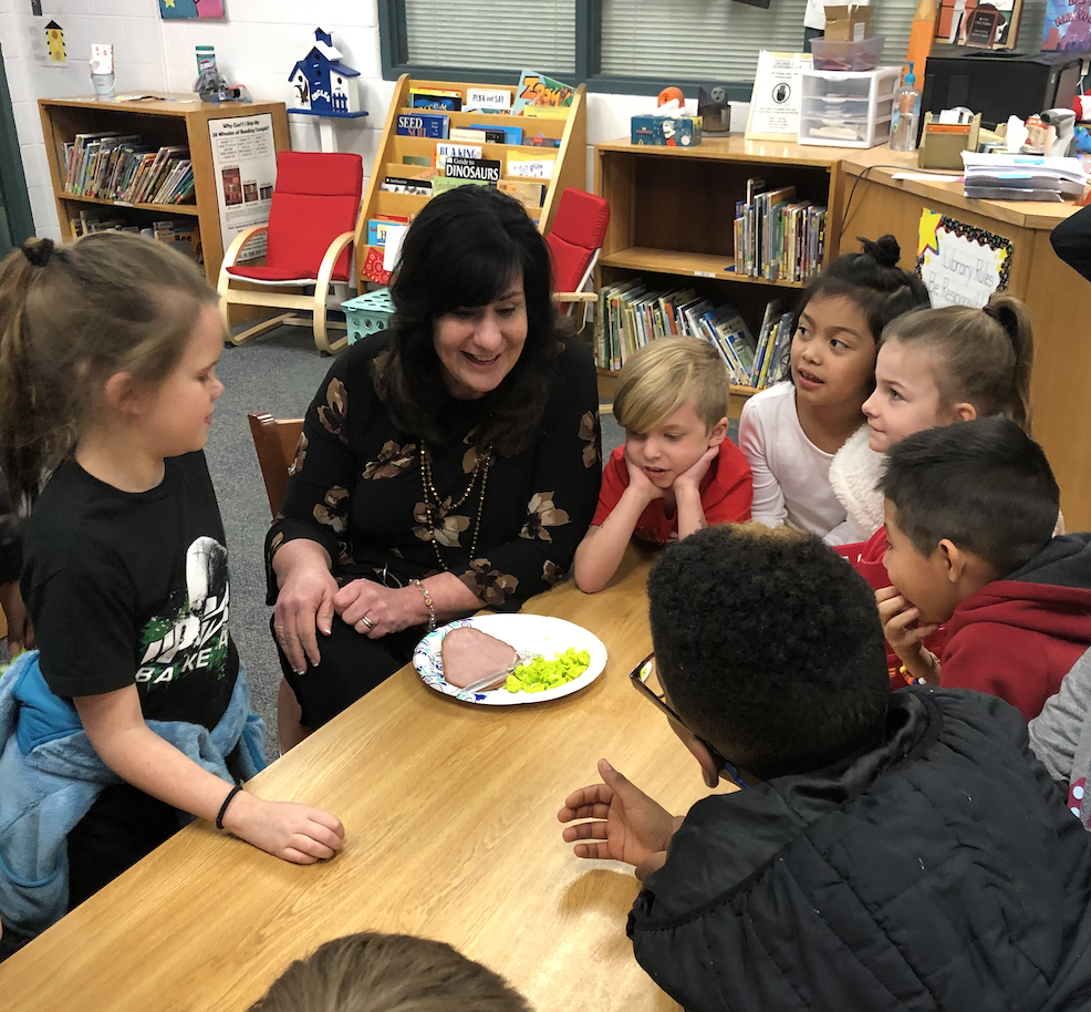 Principal eating green eggs and ham with students