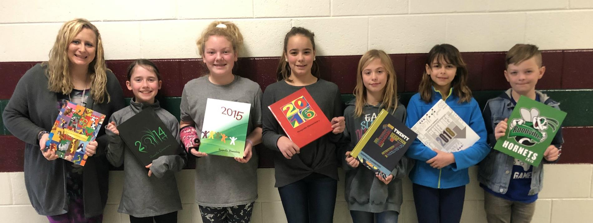 Yearbook Design Team holding past yearbooks