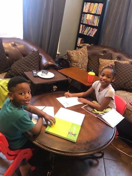 Jadon and Maya working on book reports.