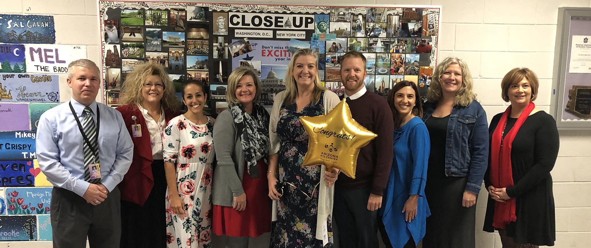 staff stands with new Board Certified Teacher