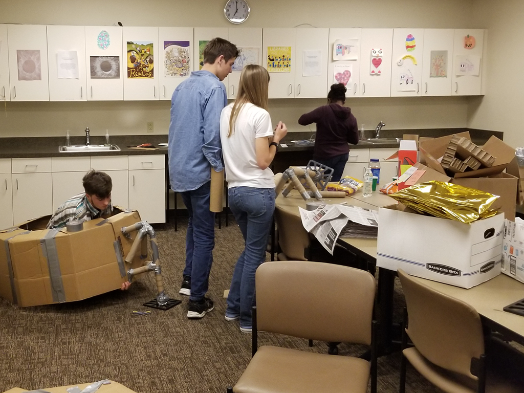 4 teens working on various parts of the lunar module in different areas of the library classroom