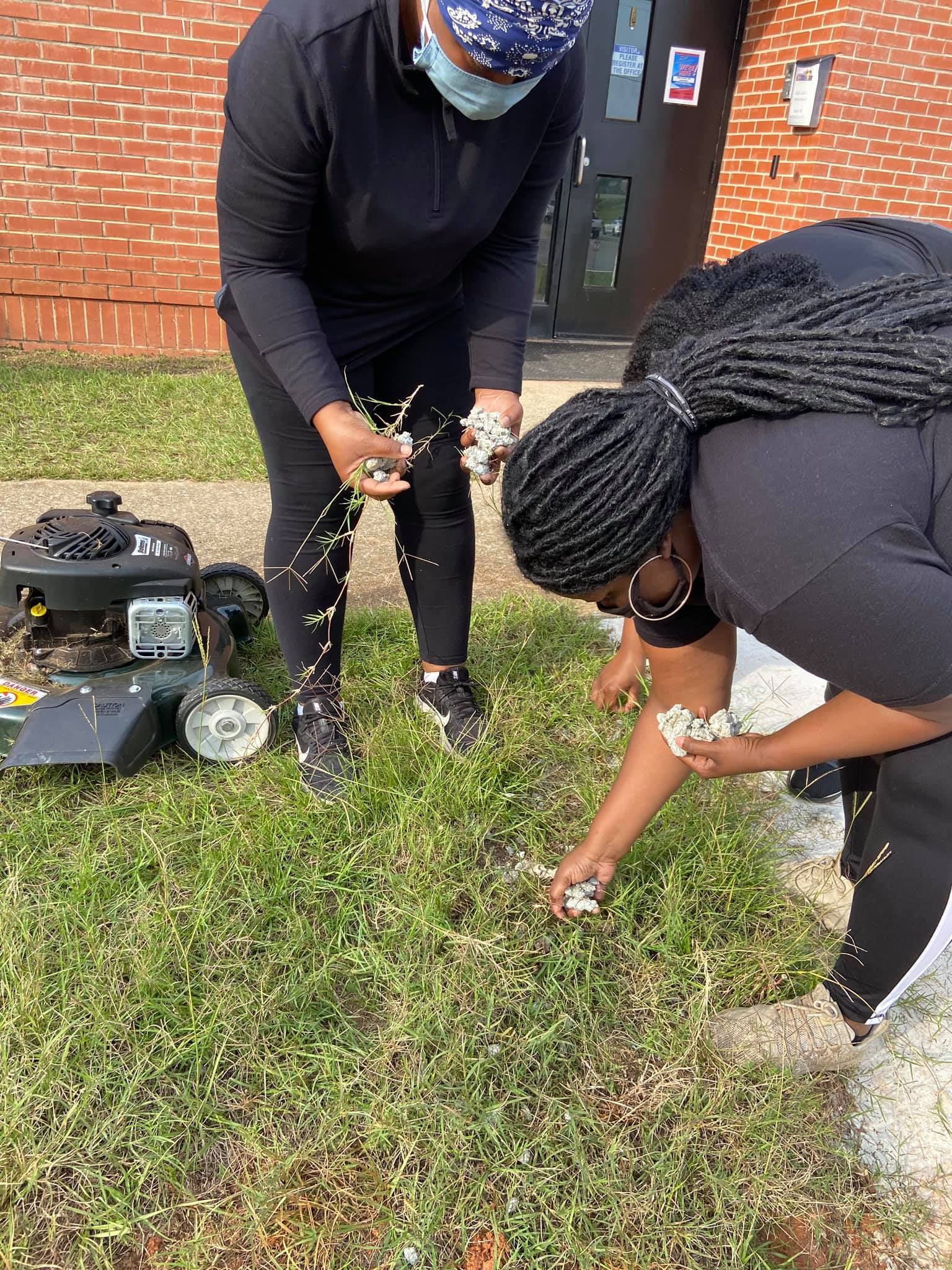 Ms. Starling and Jones clearing the grass of rocks and other debris to cut the grasss.
