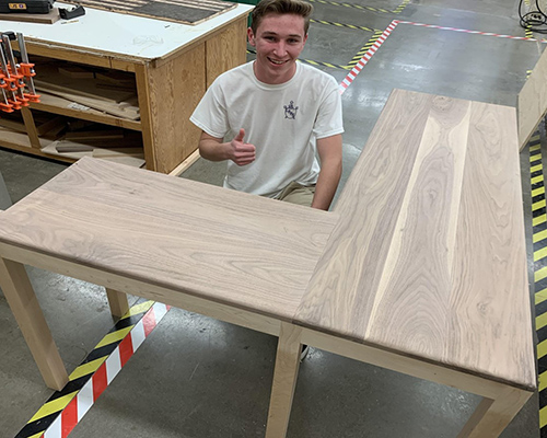 student with desk made in woodworking class