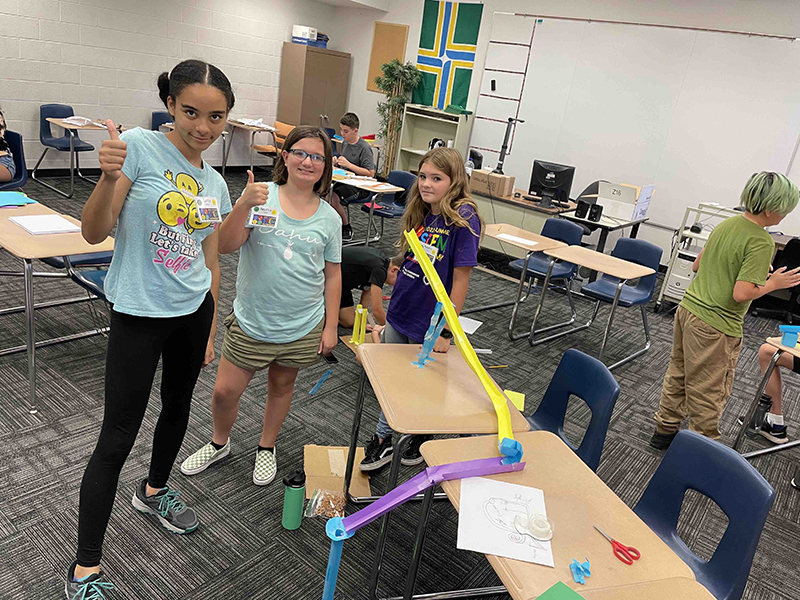 girls show off their STEM Academy project