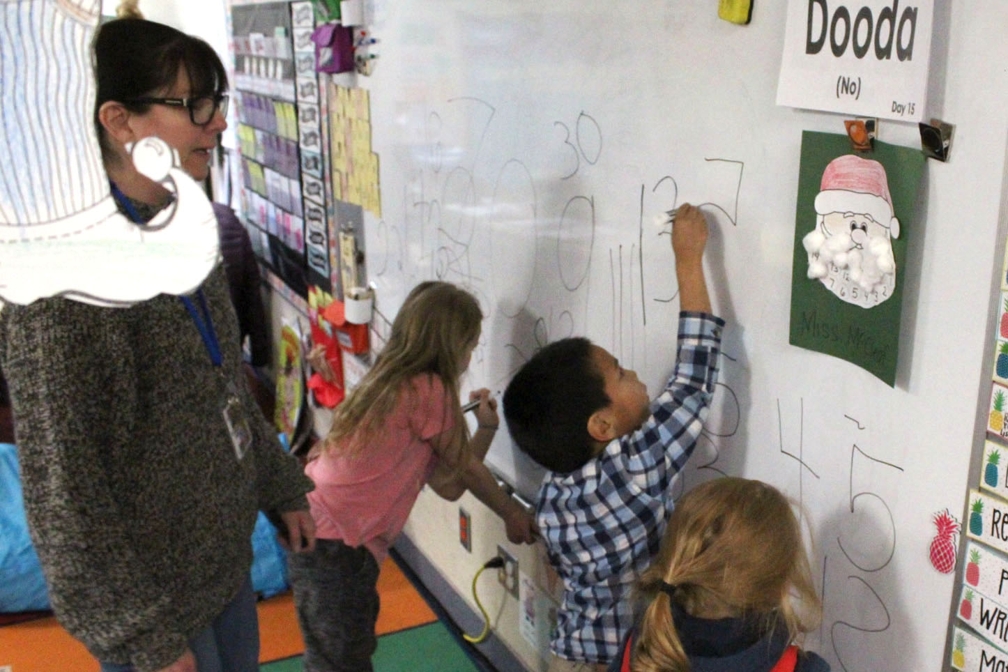 kids with teacher at whiteboard