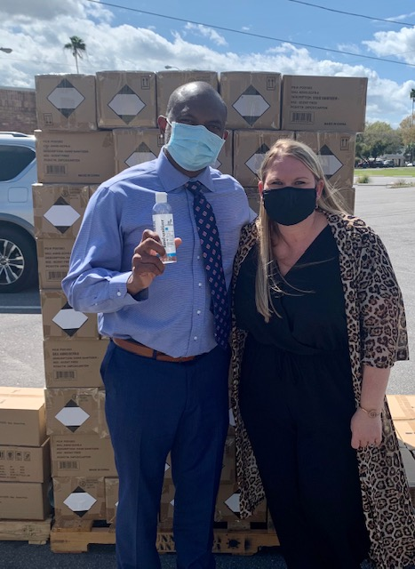 Mrs. Rose and Mr. Smith standing in front of the Advent Health hand sanitizer donation.