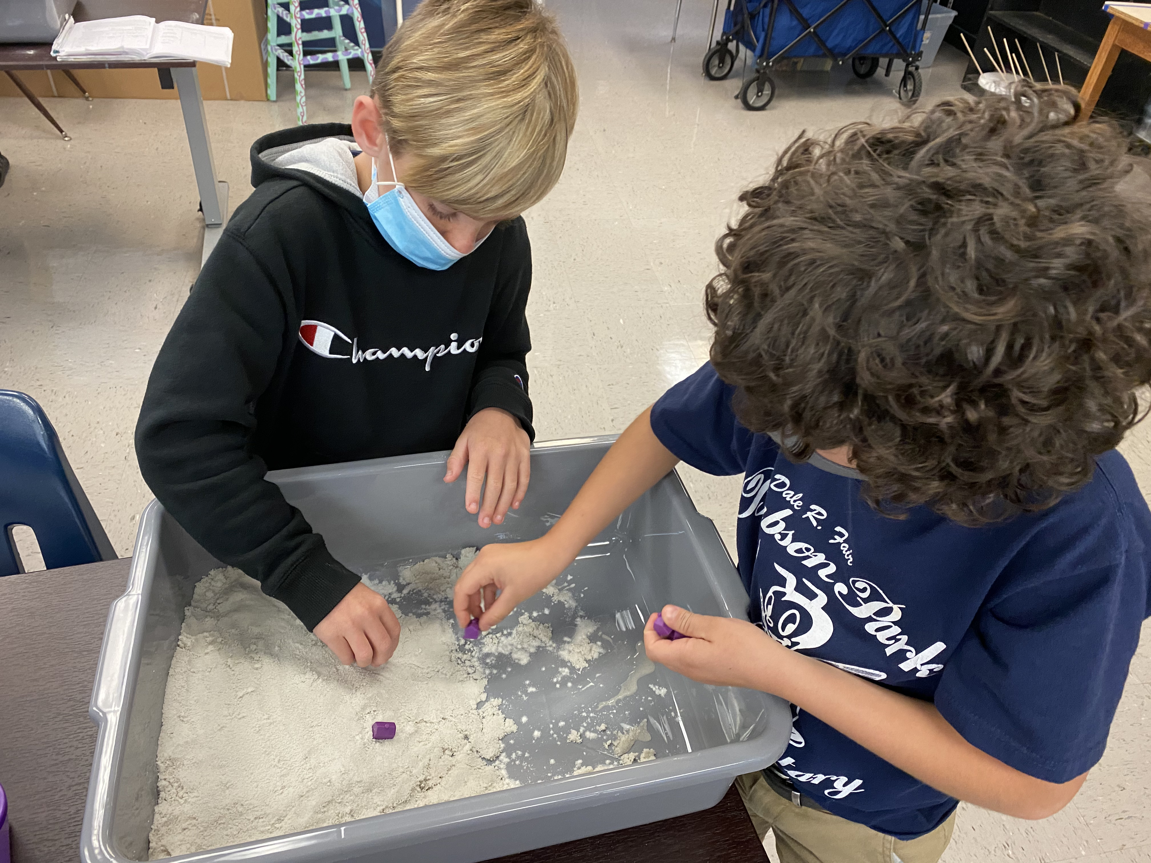 Students using sand to explore weathering and erosion