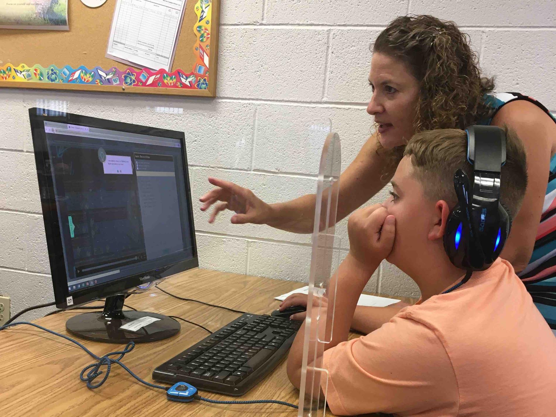 boy and teacher work on coding during STEM Academy