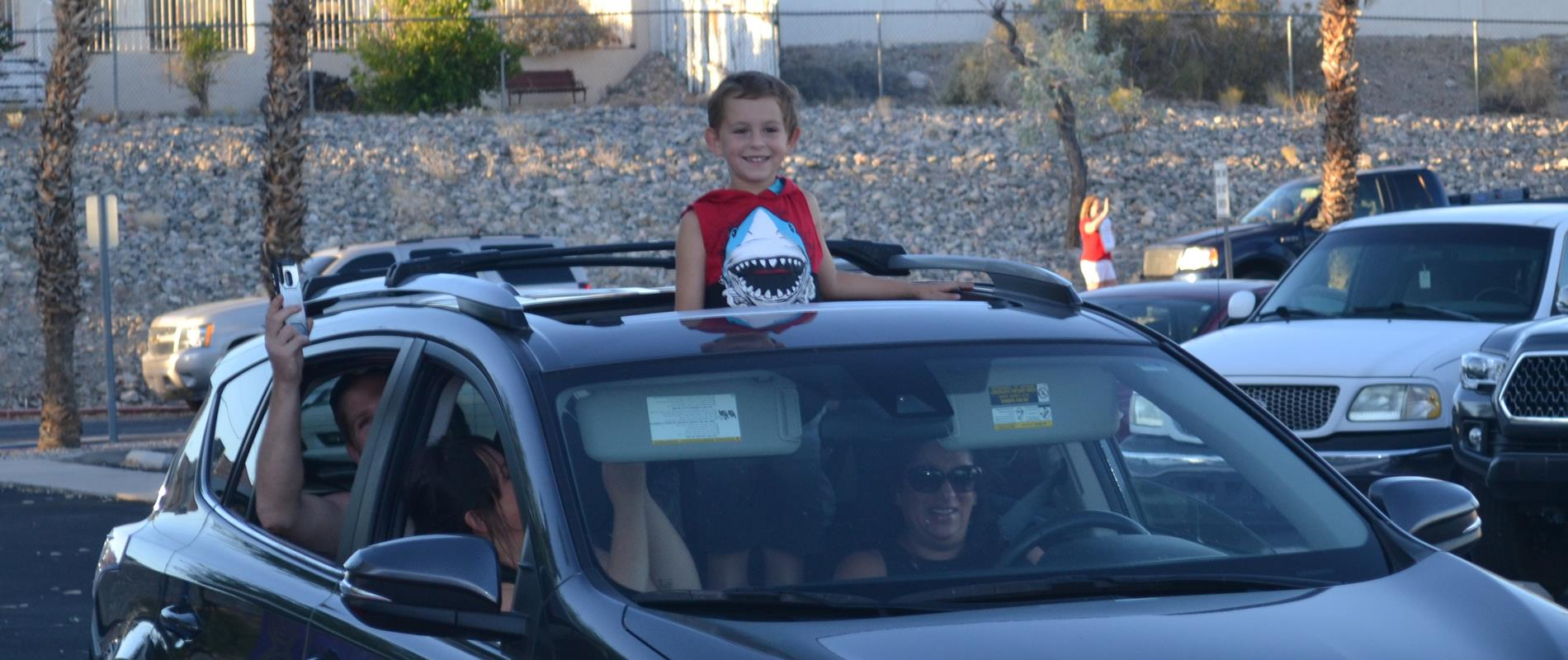 picture of boy standing through car sunroof at kindergarten graduation drive-thru