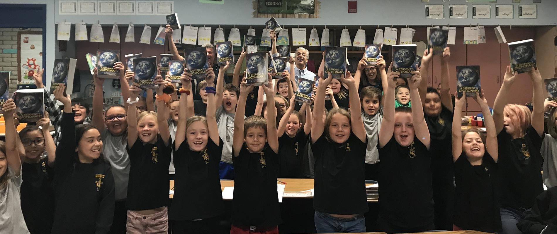elementary class holding up donated dictionaries
