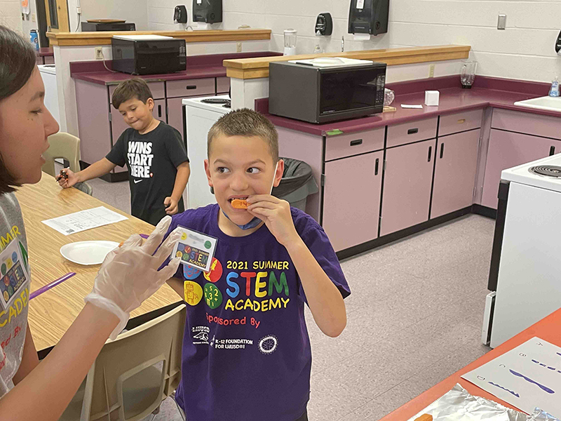 boy performs experiment during STEM Academy