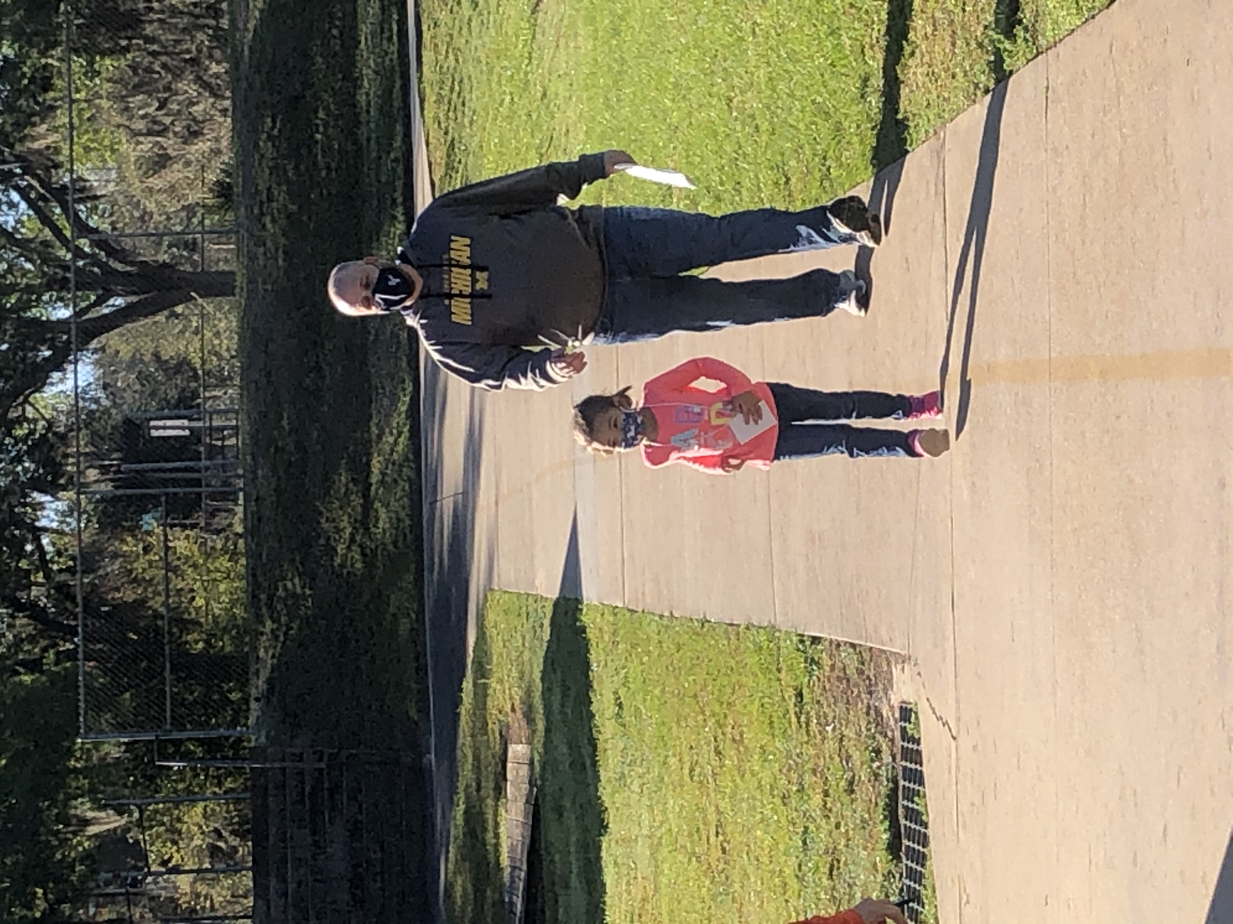 Mr. Barker and his daughter walking laps together at the Walk-a-Thon