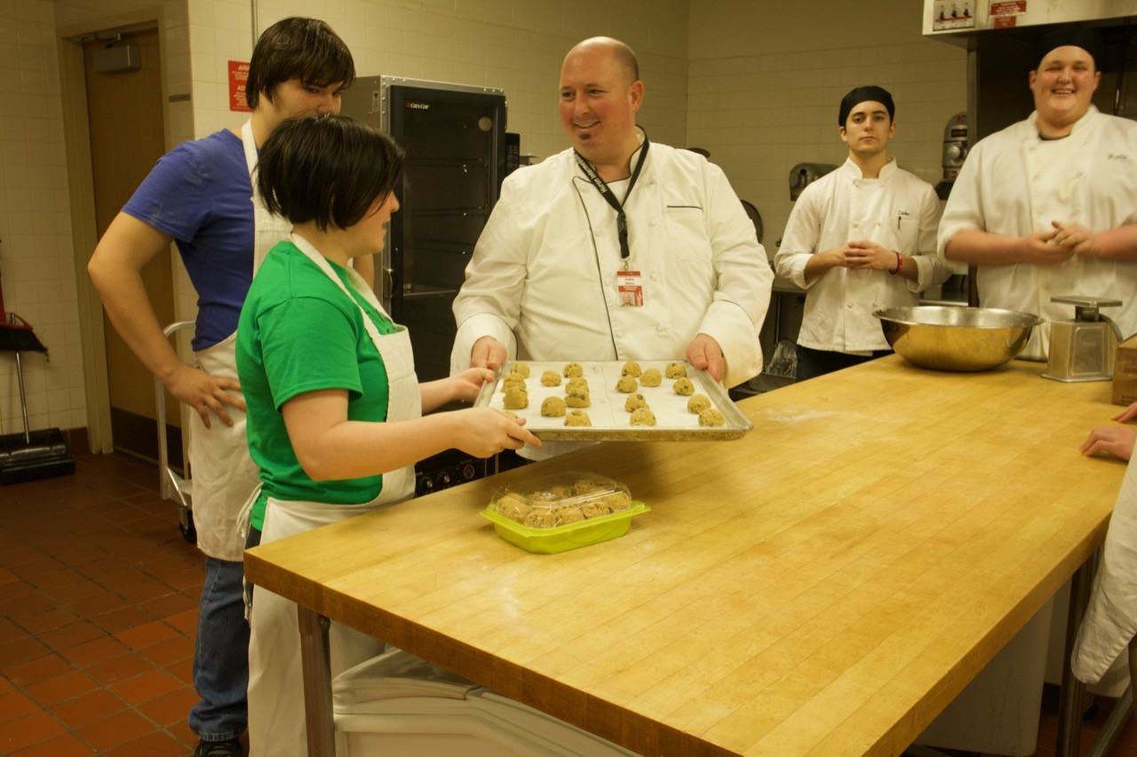 Mr. Miles working with students in the kitchen