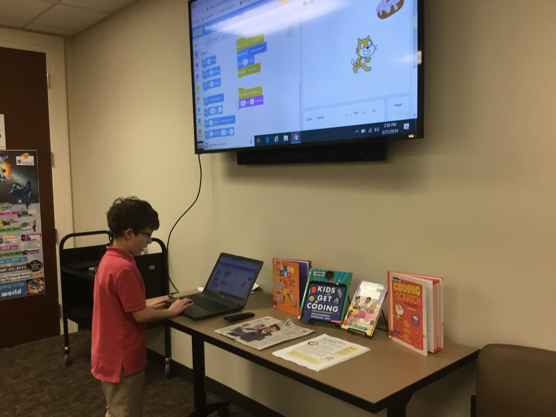 Child at table with coding books on display working on laptop in front of large display screen