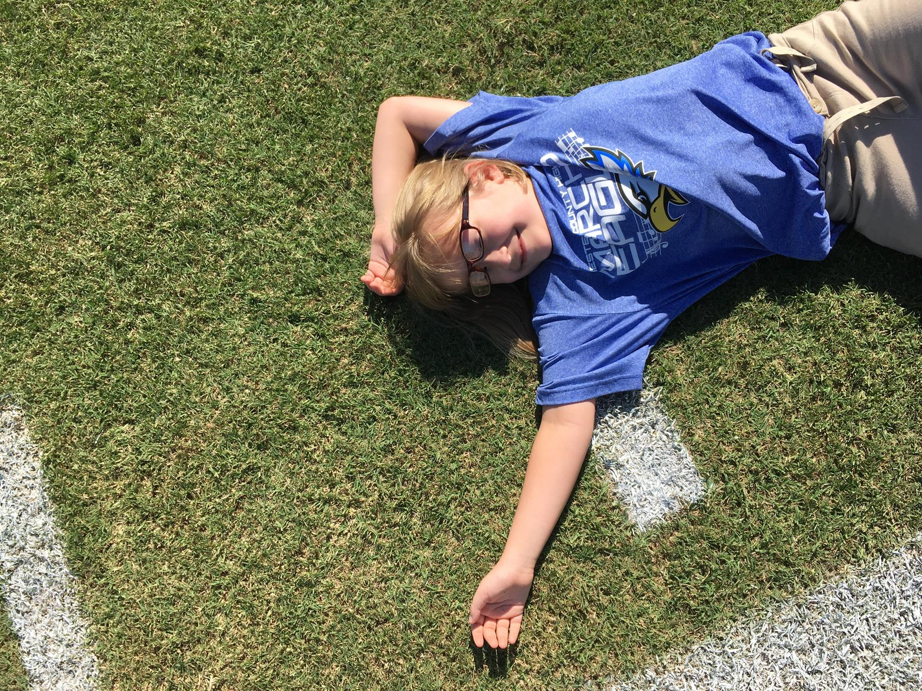 Students lays down on the football field.
