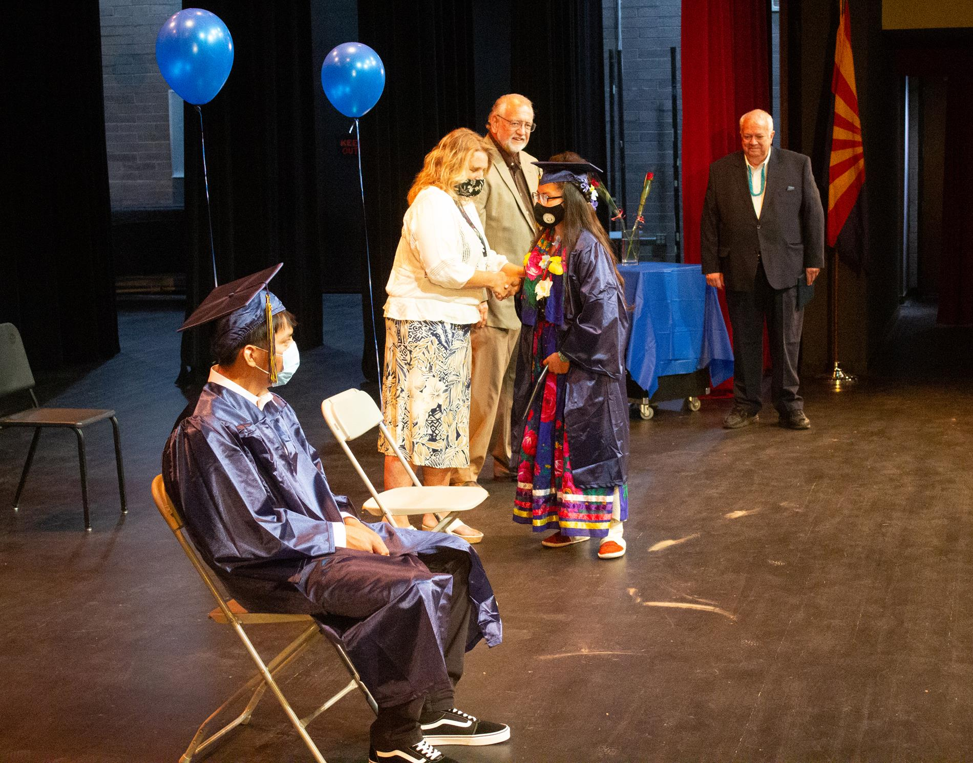 Staff congratulates a graduate.