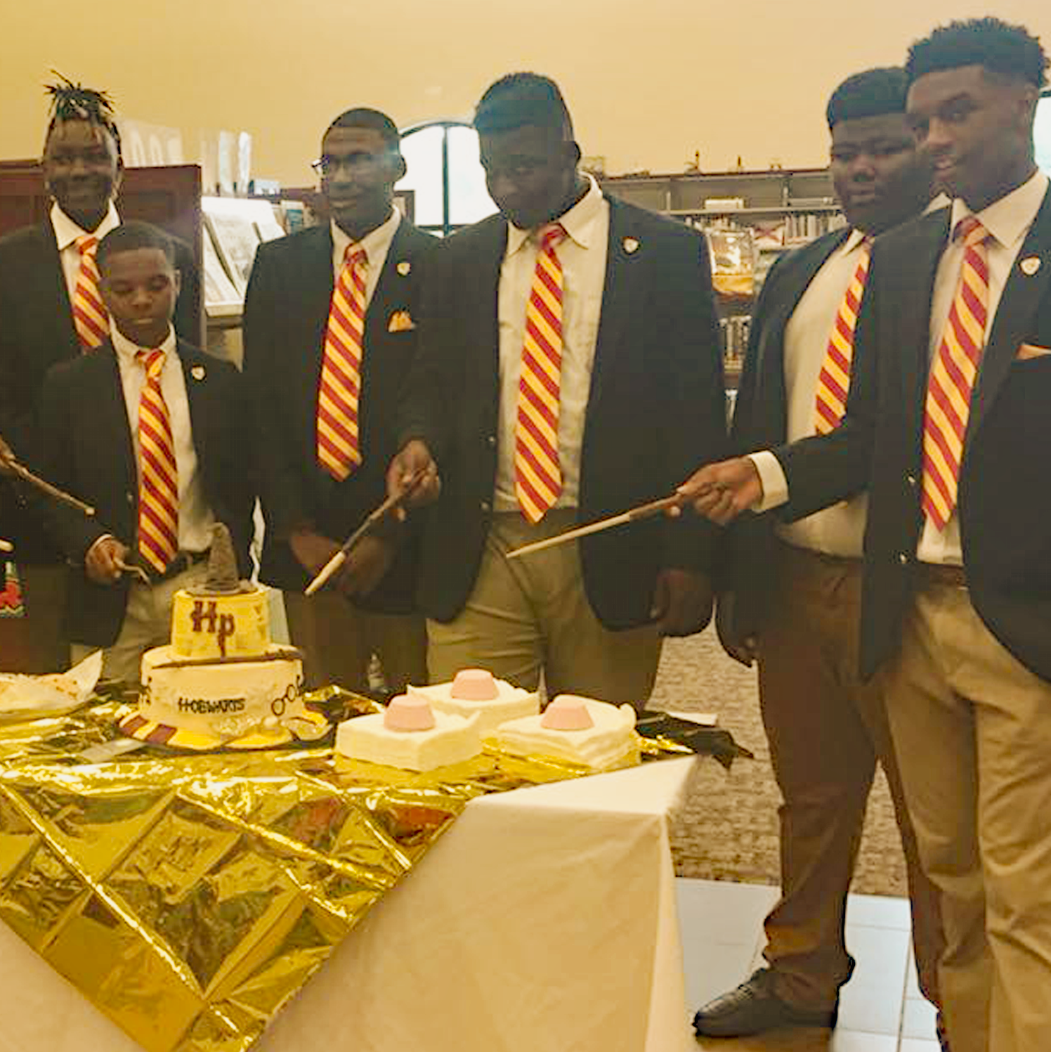 HP Night photo of Daphne boys fraternity dressed in suits for a photo shoot pointing wands at the Harry Potter birthday cake.