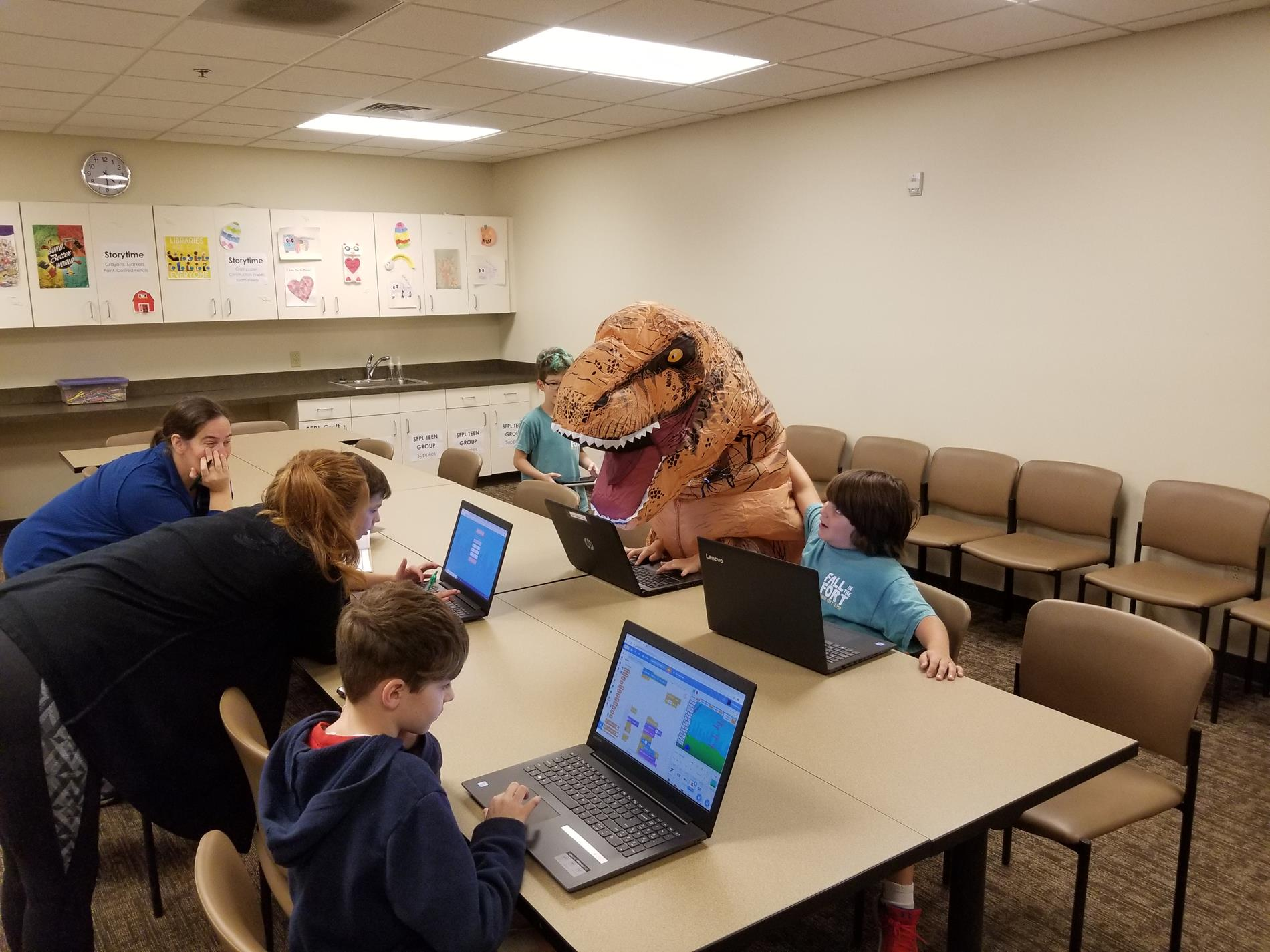 Children and a child in an inflatable T-rex costume sitting at tables working at open laptops