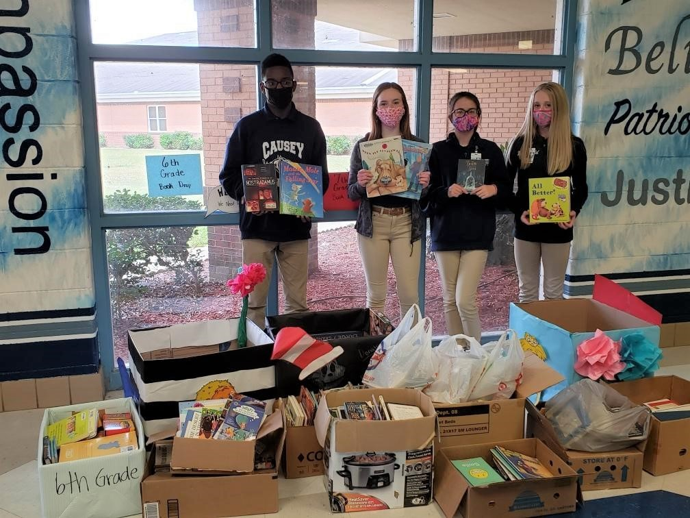 students with books collected for book drive