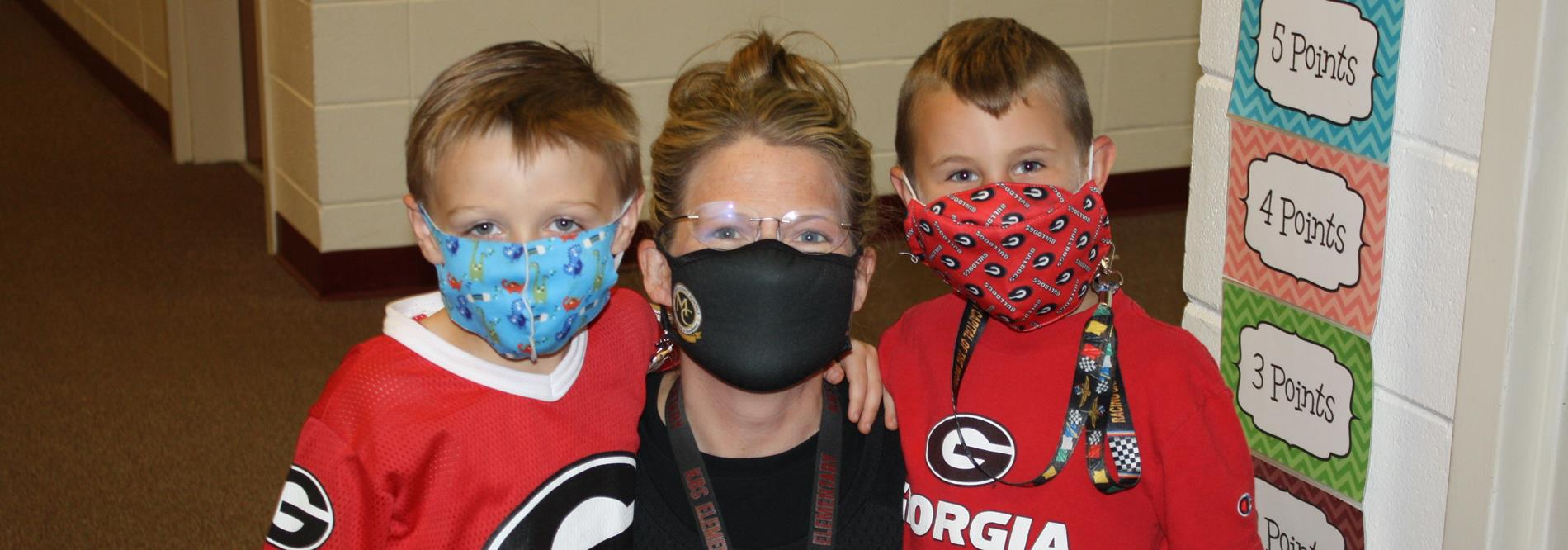 A teacher and her students pose with their GA Bulldogs clothing.