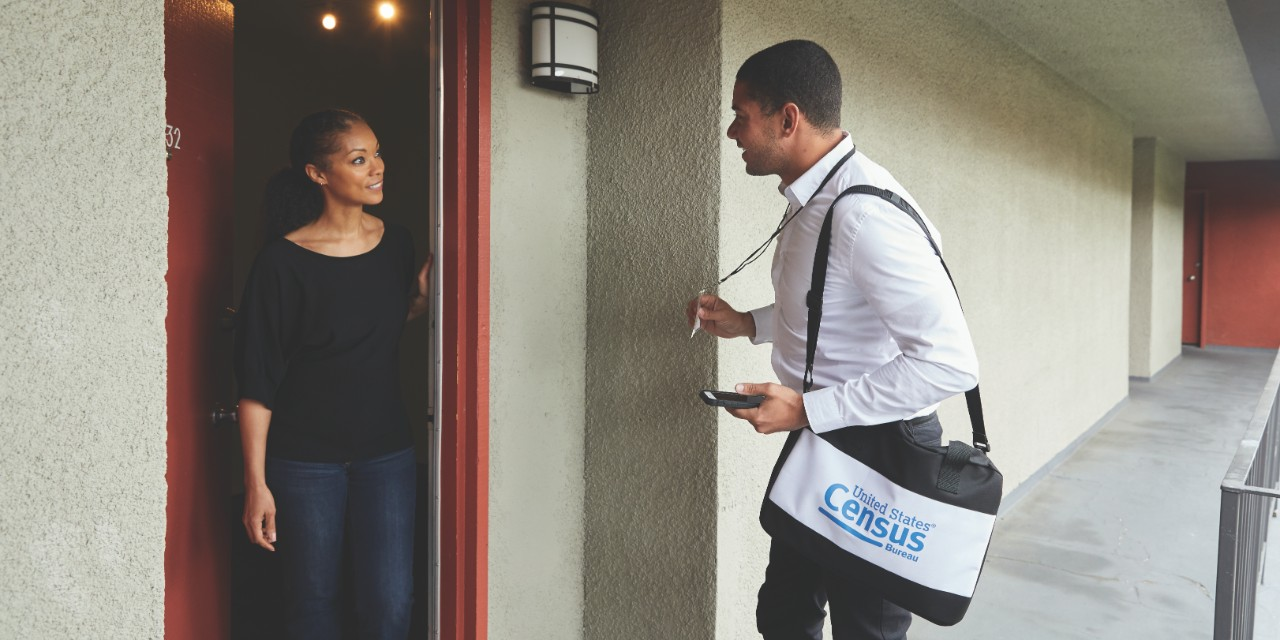 Census 2020 employee standing at door speaking to a person at their home.