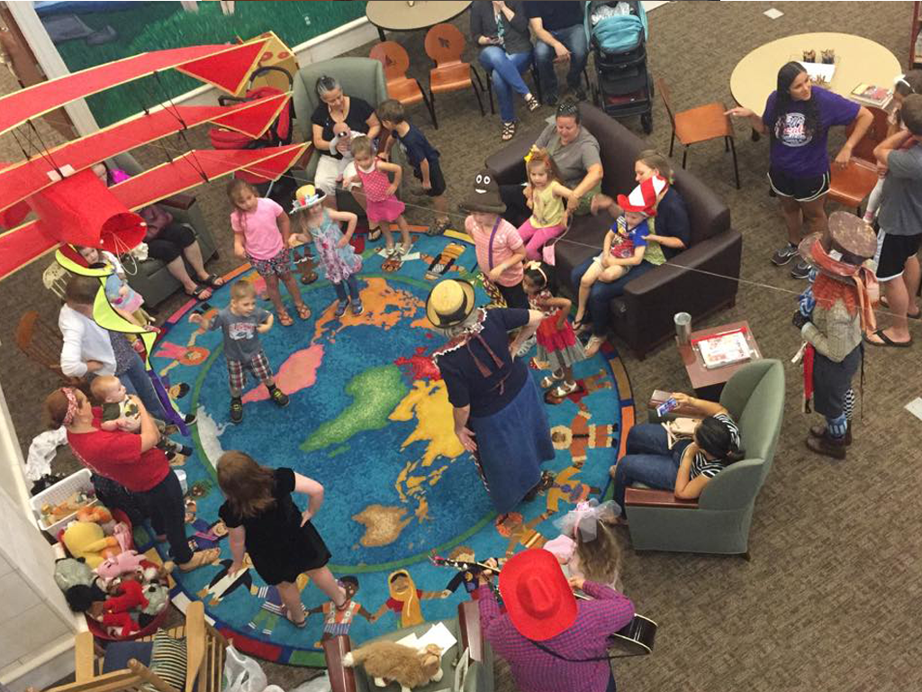 Families gathered at the Storytime rug area at SFPL for the Mad Hatter Storytime