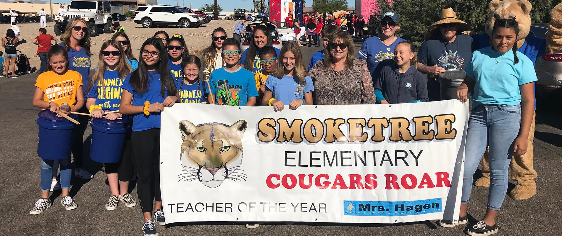 picture of students and staff holding their school parade banner