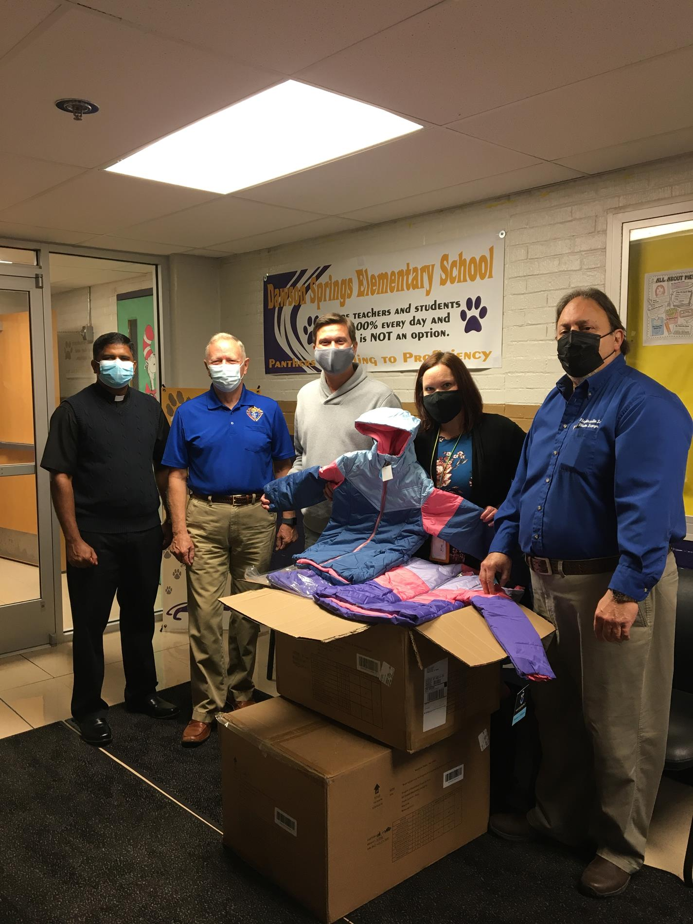 The Knights of Columbus Blessed Trinity Council donated 24 coats to the Dawson Springs Family Resource and Youth Service Center on Monday. Pictured from left are Father Jojy Joseph, District Deputy George Barber, FRYSC director Jonathon Storms, program assistant Melinda Coates and Grand Knight Tony Sicari