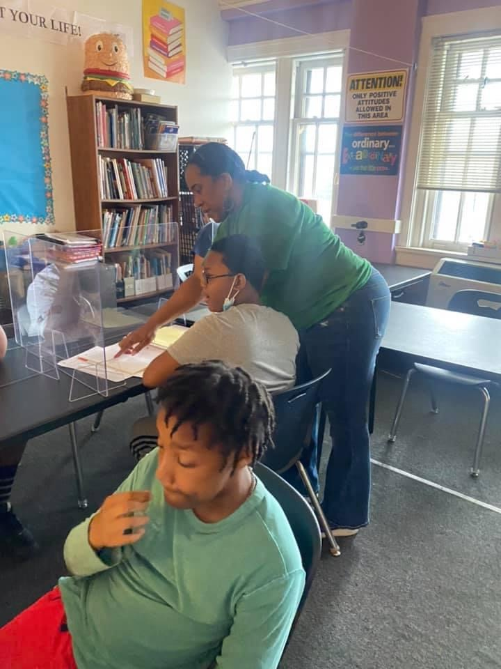 Teacher helping student read a book