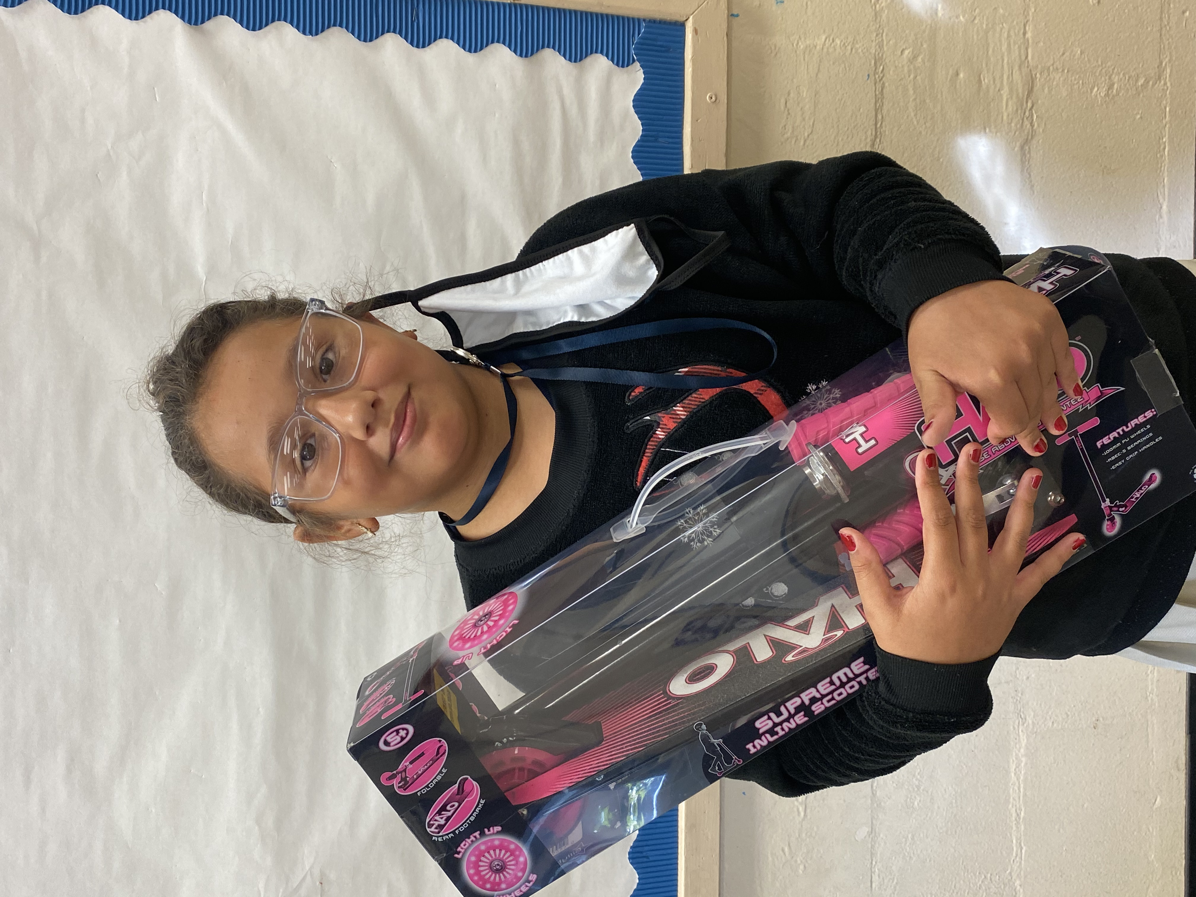 A student holding the Halo Scooter they won.