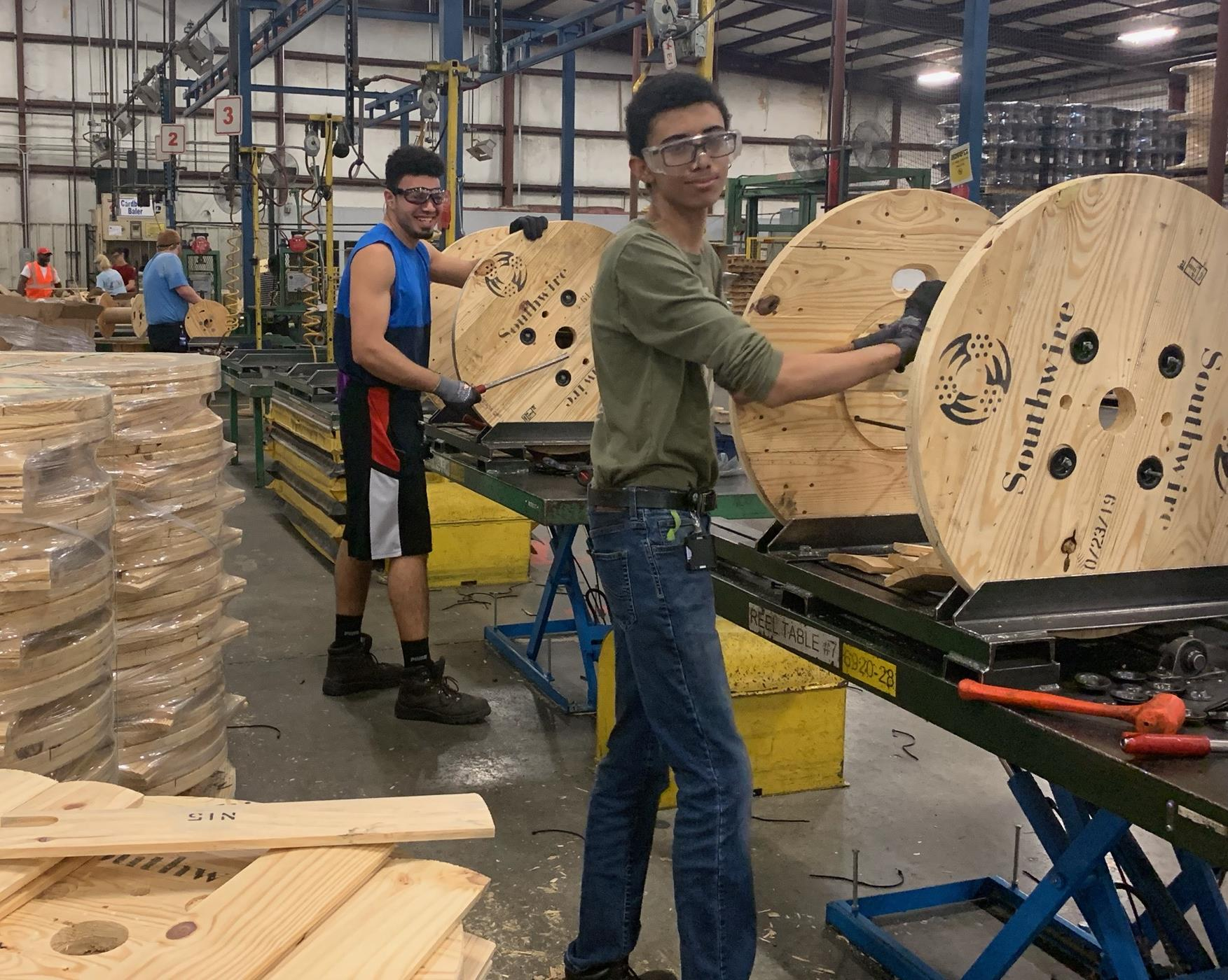 Students build wooden reels that are shipped to other plants for wire spooling