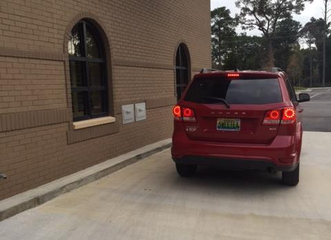 vehicle stopped at drive thru drop box located outside the library on the west side of the Spanish Fort Community Center building