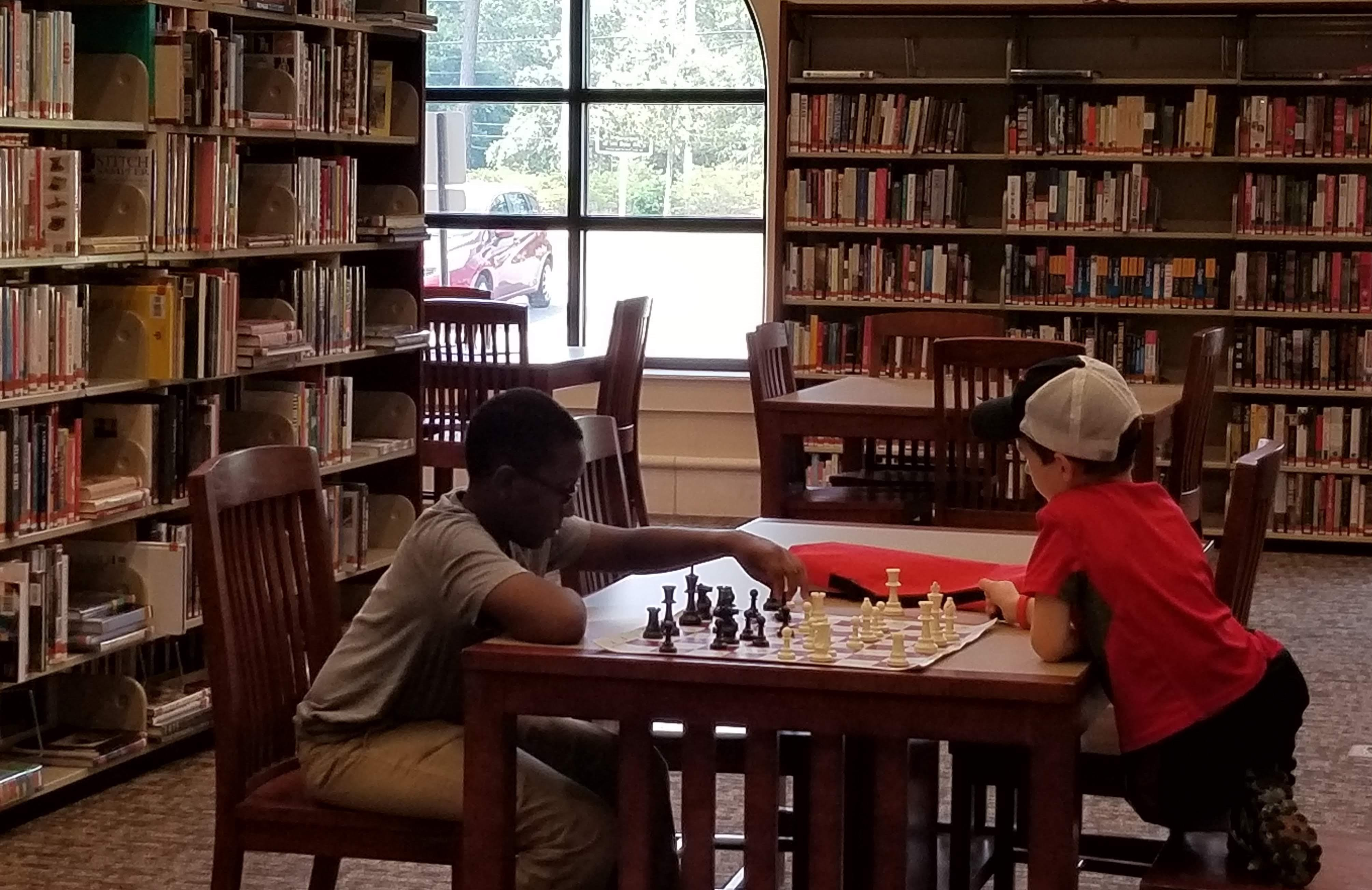 Two young boys playing chess at a table inside SFPL