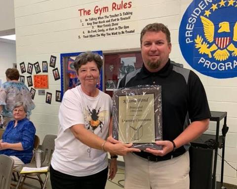 Brandon Bond accepting the plaque on behalf of his mother, Mrs. Kinma Bond