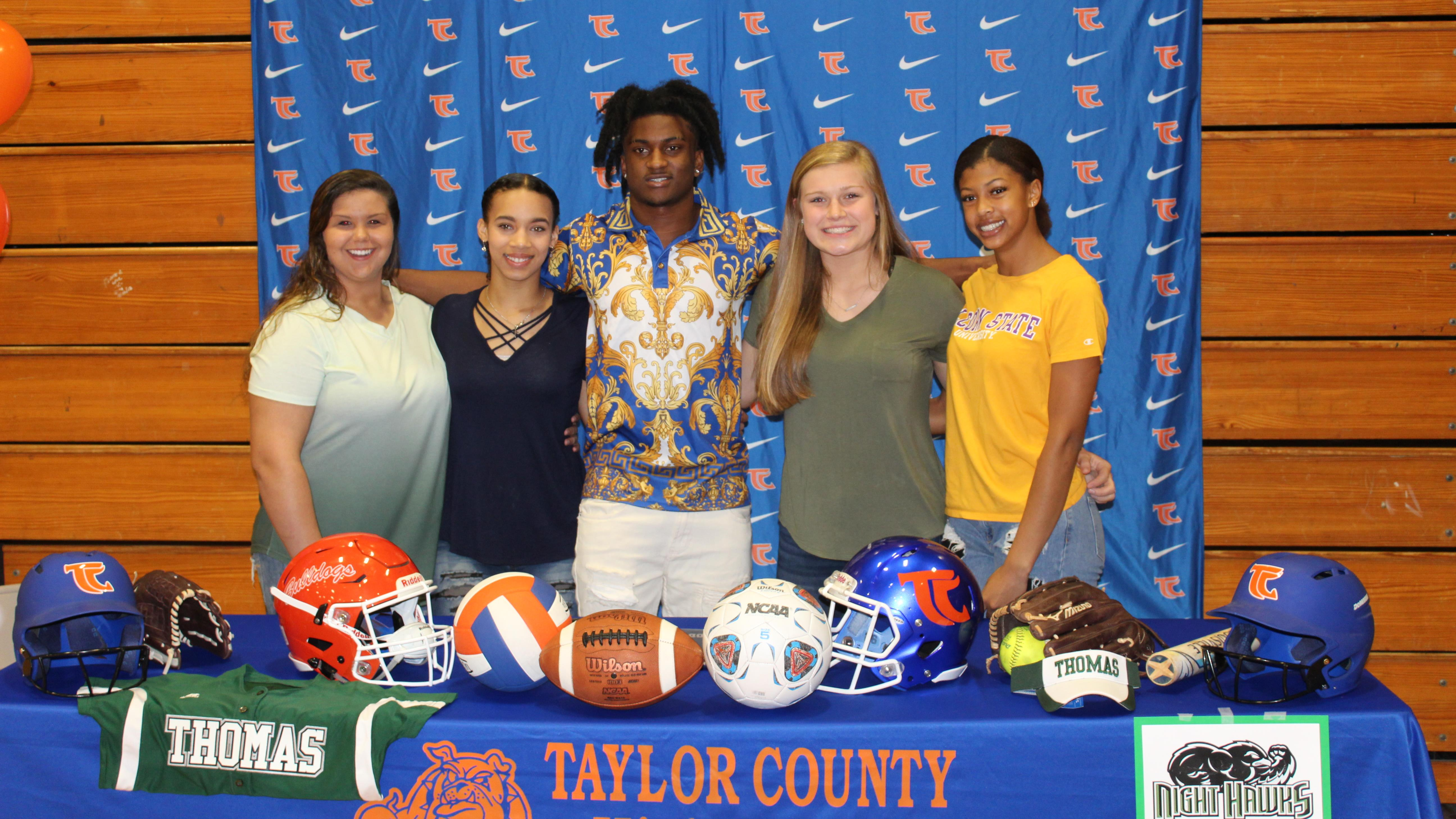 From left to right: Ann Marie McAfee, Tailor Gillyard, Robert Glanton, Jordan Pyke, Ceven Kidd at their college signing ceremony. Jordan and Ann Marie are planning to attend Thomas University to play softball. Academy. Ceven is going to Alcorn State University for soccer. Tailor will be attending __ to play both volleyball and softball. Robert is going to play football for the Air Force