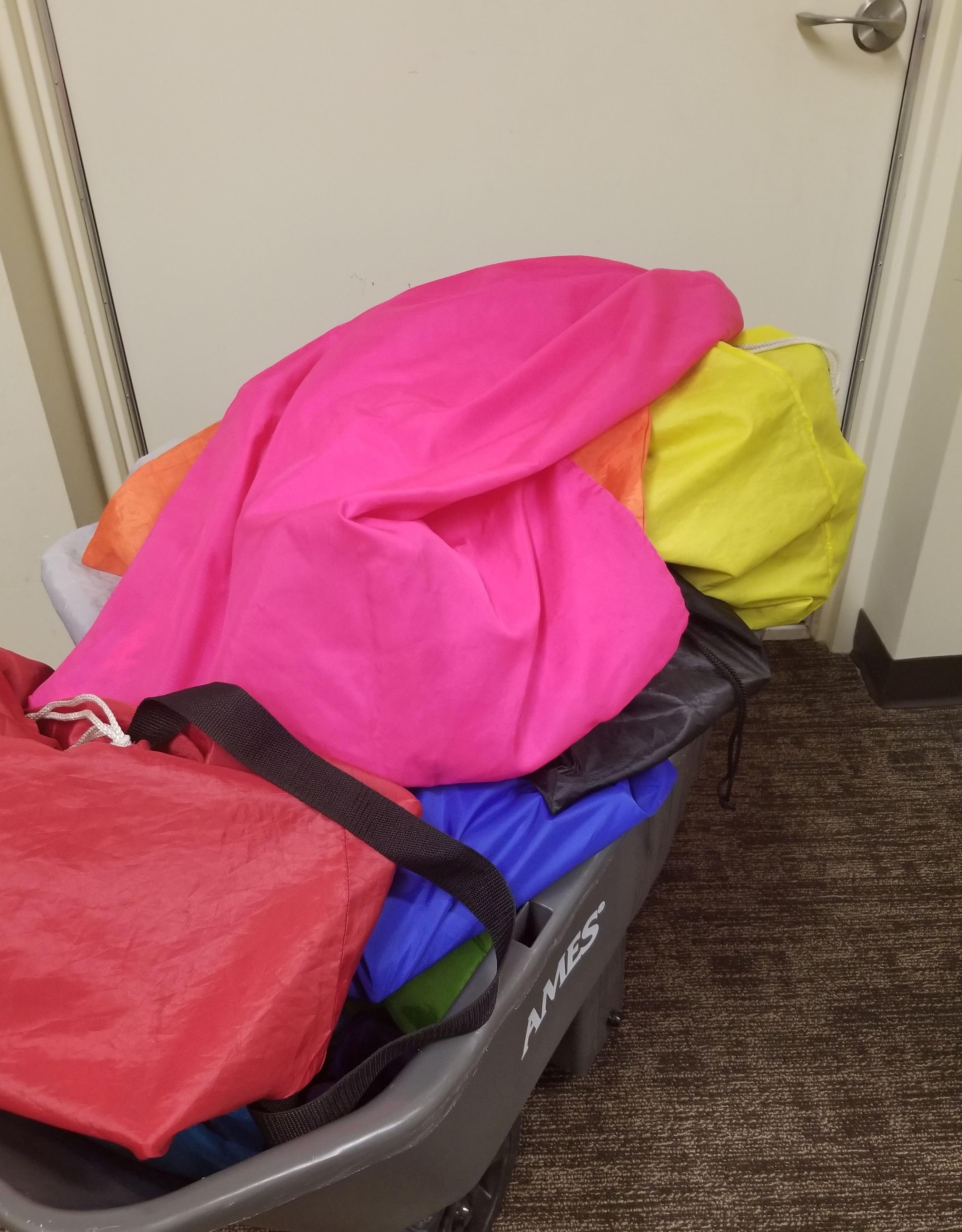 gray cart heaped with brightly colored cargo bags parked in front of a an exit door.
