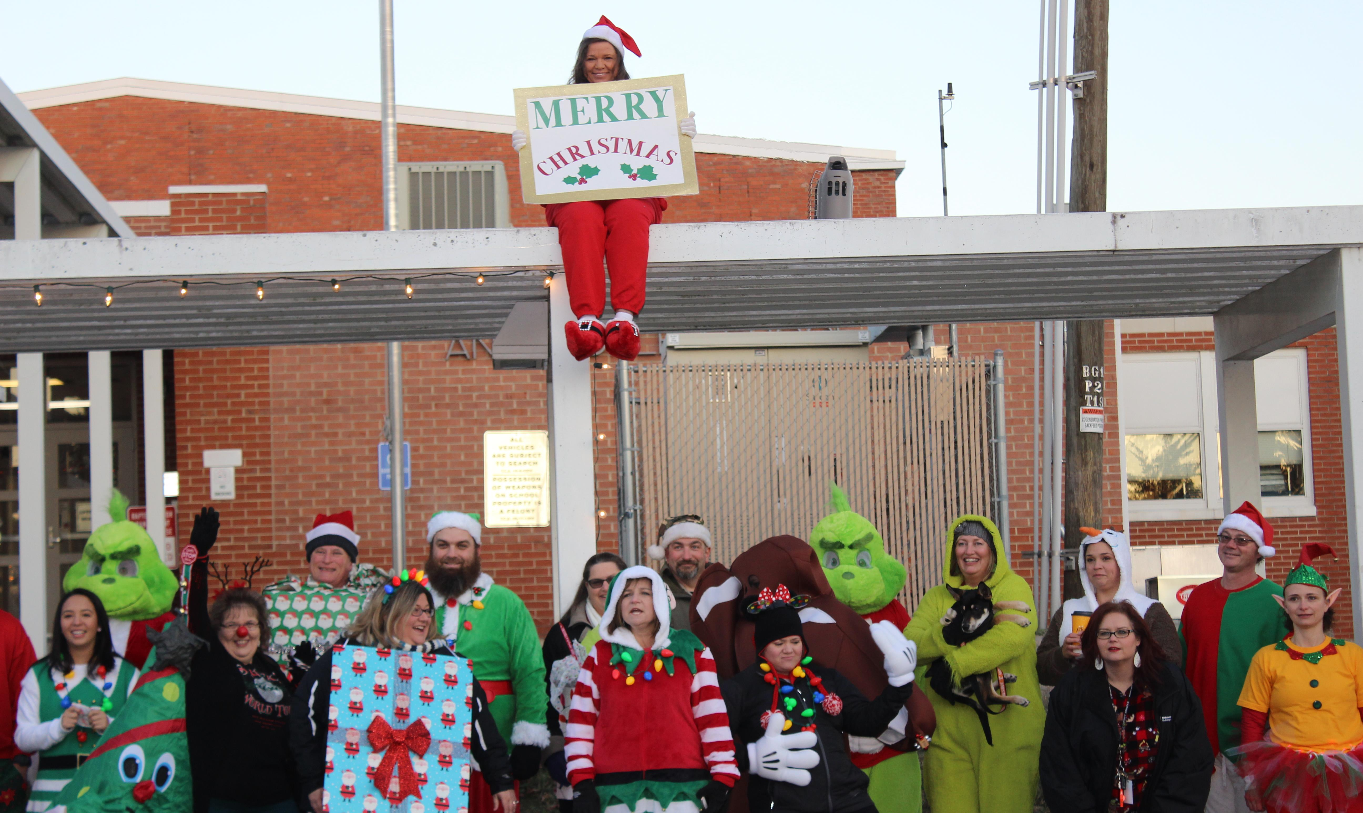Teachers in costume greeting students outside before Christmas Break