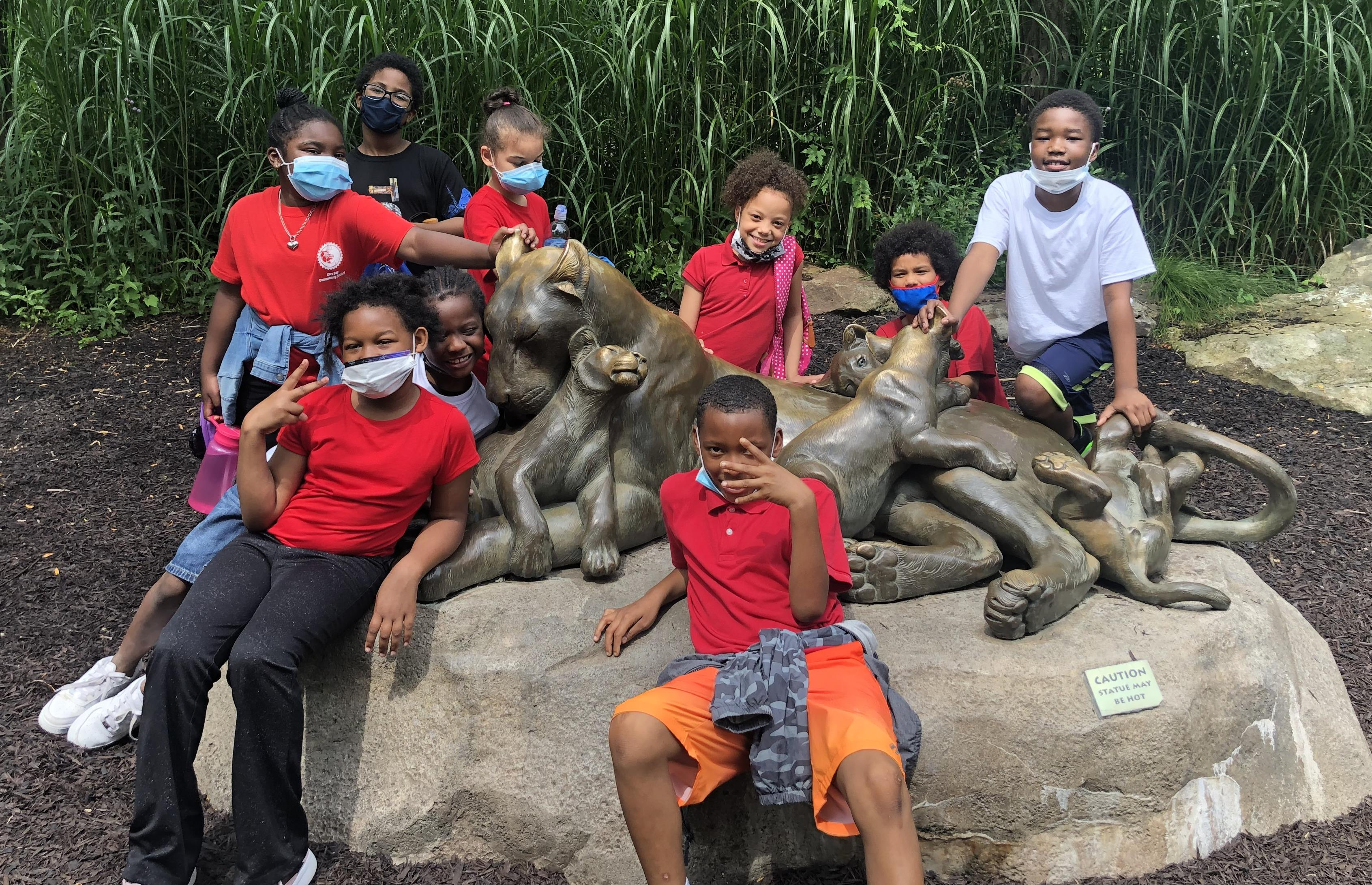 Students posing on lion statue at the zoo