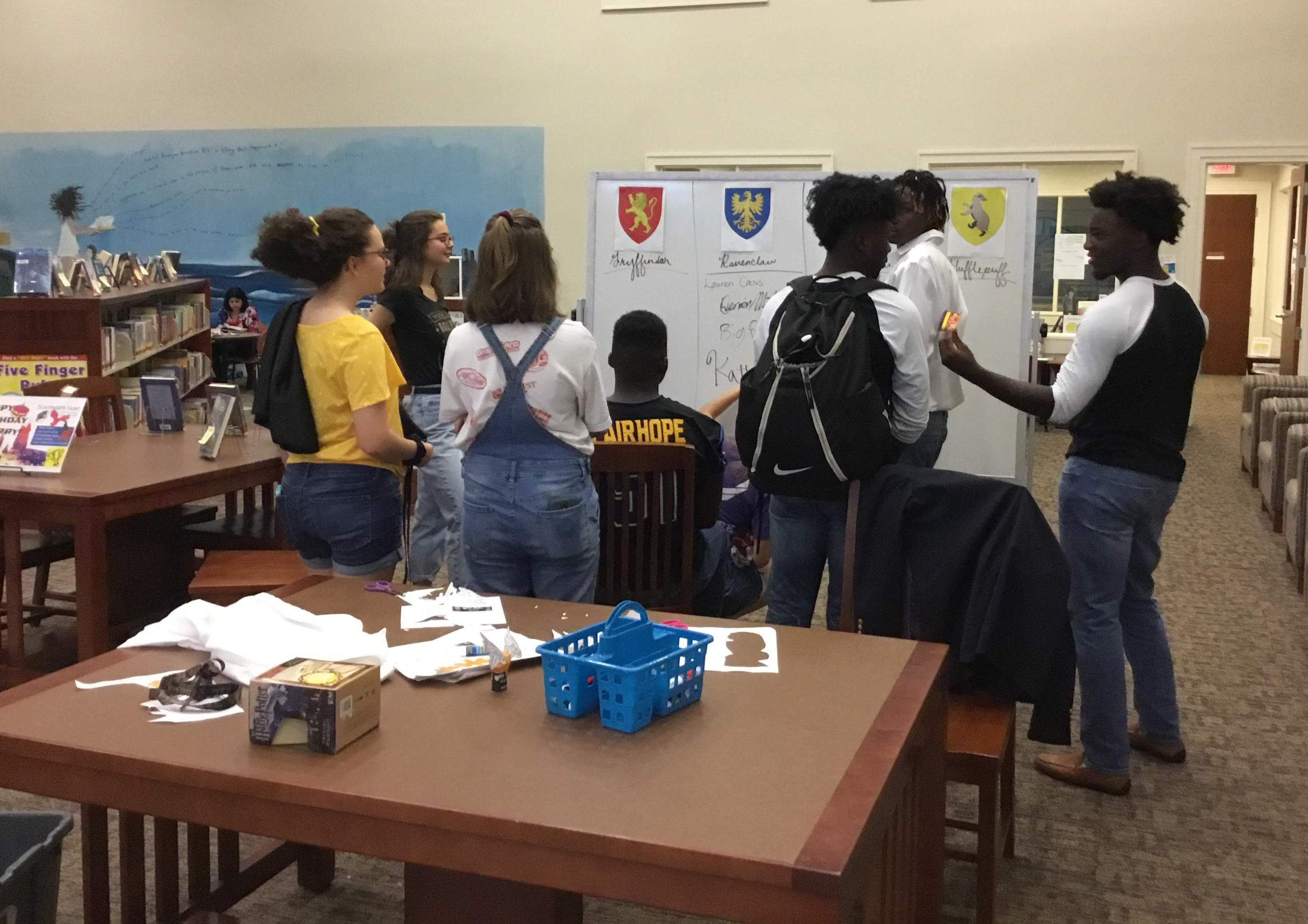 Community teens writing their names under their house name at the Harry Potter Event at SFPL in July 2018